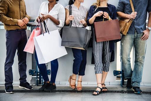 Osoby wracające z zakupów z torbami papierowymi z logo firmy